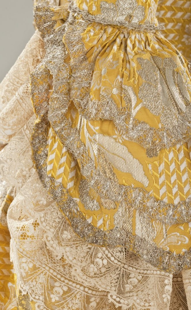 Detail sleeve, robe à la Francaise, England, c. 1760. Yellow silk plain weave with weft-float patterning and silk with metallic-thread supplementary-weft patterning, and metallic lace.